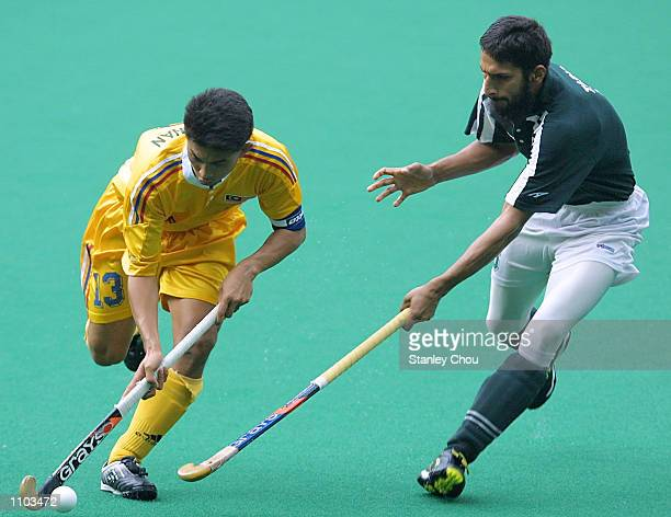 Mirnawan Nawawi of Malaysia is pursuit by Tariq Imran of Pakistan during the 58 World Cup Hockey playoff match between Malaysia and Pakistan held at...