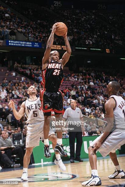 Point guard Anthony Carter of the Miami Heat rebounds the ball as point guard Jason Kidd of the New Jersey Nets plays defense during the NBA game at...