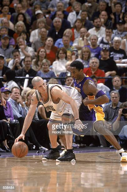Point Guard Mike Bibby of the Sacramento Kings dribbles while maneuvering for position while Guard Kobe Bryant of the Los Angeles Lakers defends...