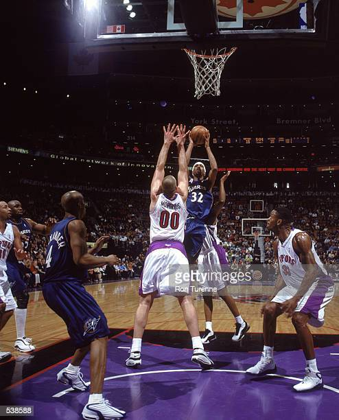 Richard Hamilton#32 of the Washington Wizards shoots for a basket as he is blocked by Eric Montross of the Toronto Raptors during the game at the Air...