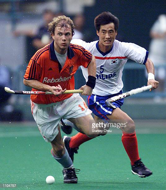 Teun de Nooijer of Netherlands is pursuit by Kim Yong-Bae of Korea during the World Cup Hockey 3rd placing playoff match between Netherlands and...