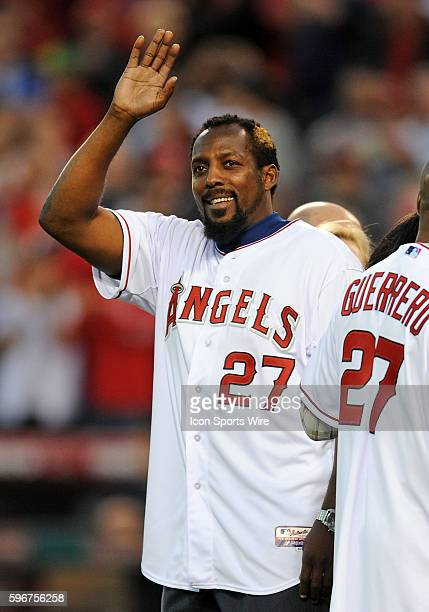 Former Angels player Vladimir Guerrero waves to the fans before throwing out the first pitch of an opening day game between the Los Angeles Angels of...