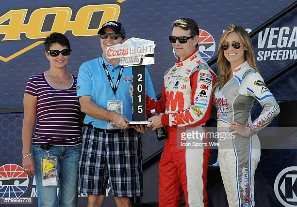 NASCAR Sprint Cup driver Jeff Gordon posses for photographs with the Coors Light Pole Trophy and Miss Coors Light Amanda Mertz before the start of...
