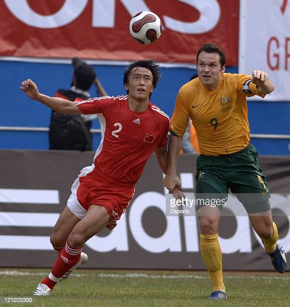 Mar 24 Guangzhou China Du Wei of China vies with Mark Viduka of Australia during a warmup football match between China and Australia Australia won 20