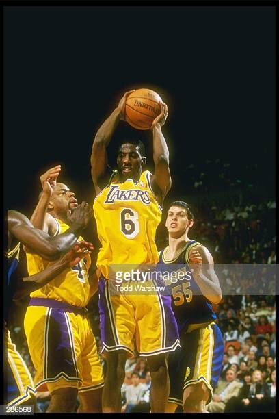 Guard Eddie Jones of the Los Angeles Lakers down the lane as teammate center Sean Rooks and forward Andrew DeClercq of the Golden State Warriors look...