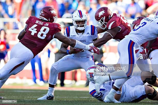 Mar Smith of the Louisiana Tech Bulldogs is sacked by Deatrich Wise Jr #48 and Jeremiah Ledbetter of the Arkansas Razorbacks at Razorback Stadium on...