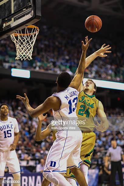 Duke Blue Devils guard Matt Jones blocks a shot by Notre Dame Fighting Irish guard/forward Pat Connaughton during the ACC Tournament at Greensboro...