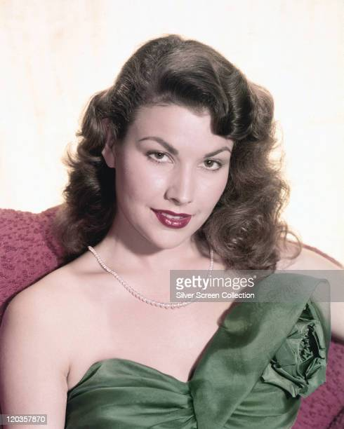 Mara Corday US actress wearing a green shoulderless gown and a pearl necklace in a studio portrait against a white background circa 1955
