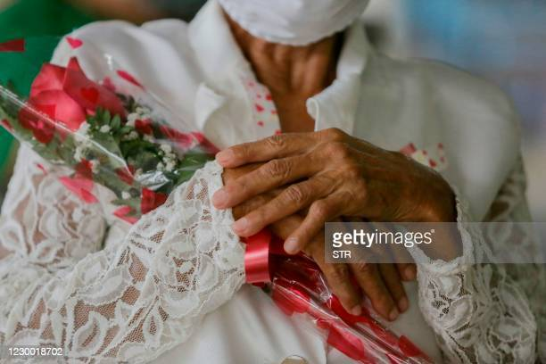 María de los Santos holds a rose during a mariachi performance at the Church of the Risen Christ during the commemoration of Mother's Day in Panama...