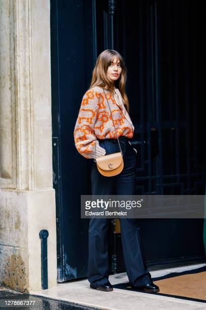 Mara Lafontan wears an oversized wool gray and orange pullover with puff sleeves and printed animals, a silk scarf, flared pants, a brown leather...