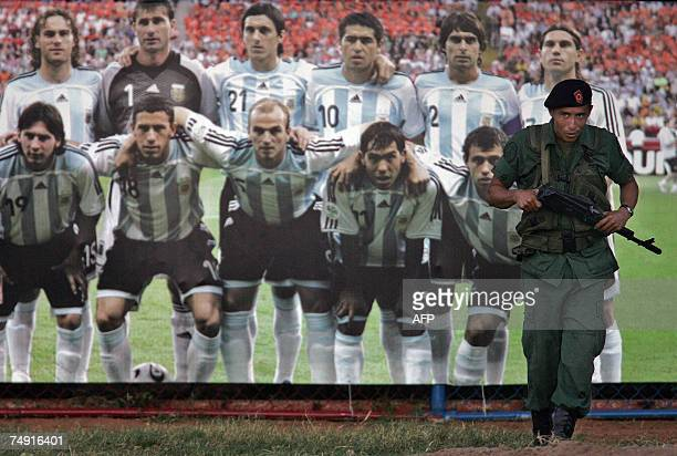 A soldier stands guard next to a poster of Argentina's national football team at the field where Argentina trains in Maracaibo Venezuela on June 25th...