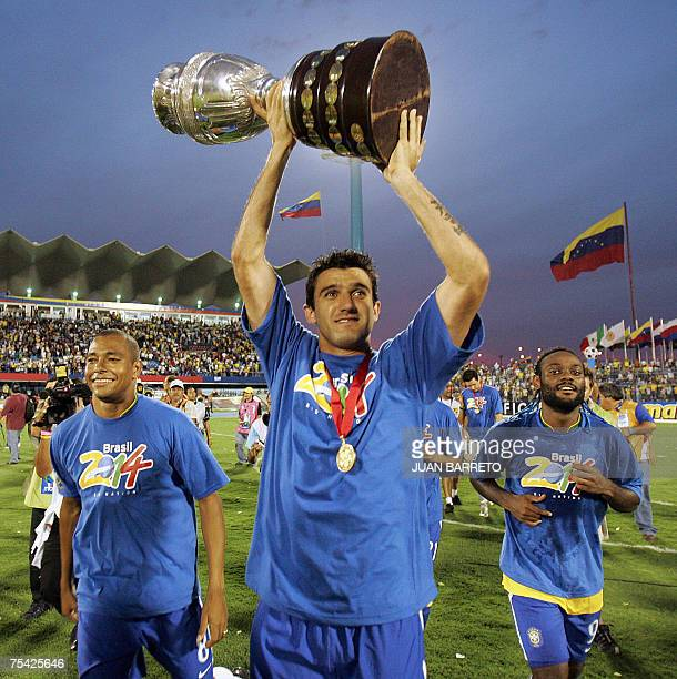 Brazilian midfielder Gilberto Silva defender Elano and forward Vagner Love celebrate with the trophy after Brazil won the Copa America 2007 final...