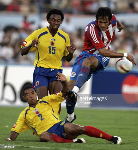 Paraguayan forward Roque Santa Cruz vies for the ball with Colombian defender Ivan Cordoba and midfielder Jhon Viafara, during the group C football...