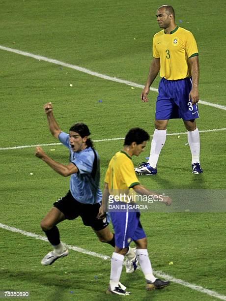 Uruguayan forward Sebastian Abreu celebrates after he scored the second goal passing Brazil's midfielder Josue and defender Alex during the...