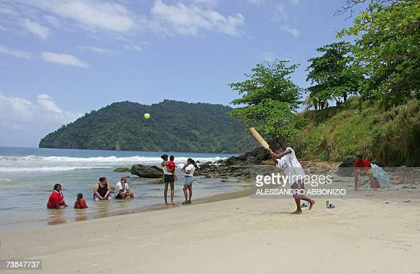 A man plays cricket with his family on the beach in Maracas Bay in northern Trinidad 11 March 2007 The group stage of the ICC Cricket World Cup 2007...
