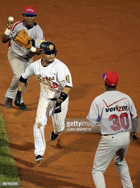 Alex Gonzalez of the Lions of Caracas gets caught in a downrun between firstbaseman Jose Offerman and second baseman Anderson Hernandez of the Tigres...