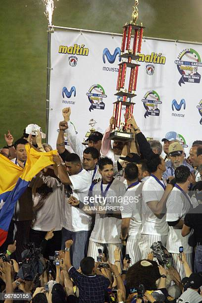 Members of the Lions of Caracas wave the country's flag and hold up the Caribbean Series trophy following their victory over the Tigres of Licey in...
