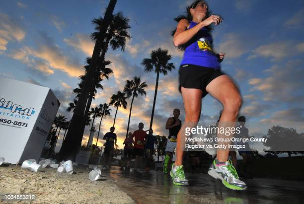 Marahoner runners pass a water station at Rainbow Harbor at the Long Beach Marathon in Long Beach CA on Sunday October 13 2013