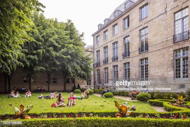 marais, people relaxing at the public park jardin de l'hôtel-lamoignon or jardin de la bibliothèque-historique - historique stock pictures, royalty-free photos & images