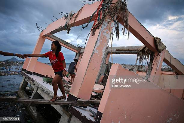 Maralyn Balickio 15 is helped across a plank of wood from what was once her home after searching for possessions on November 20 2013 in Leyte...