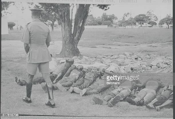 Black Rhodesian policeman walks past bodies of seven fellowRhodesiansreportedly nationalist guerillas slain Feb 17displayed in courtyard of police...