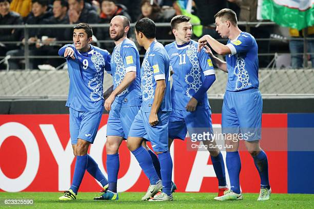 Marat Bikmaev of Uzbekistan celebrates scoring his team's first goal with his team mates during the 2018 FIFA World Cup qualifying match between...