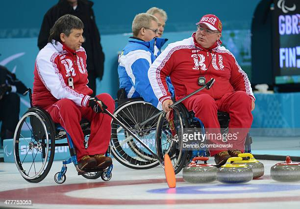 Marat Romanov and Andrey Smirnov of Russia discuss tactics during the Round Robin Session 7 during day four of Sochi 2014 Paralympic Winter Games at...