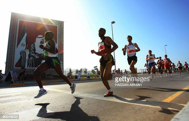 Marathon contestants run past a portrait of late Emirati leader Sheikh Zayed bin Sultan alNahayan during the Zayed International Marathon in the Gulf...