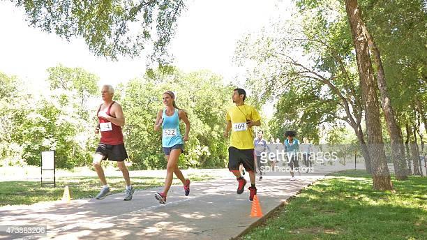Marathon race competitors running toward finish line in park