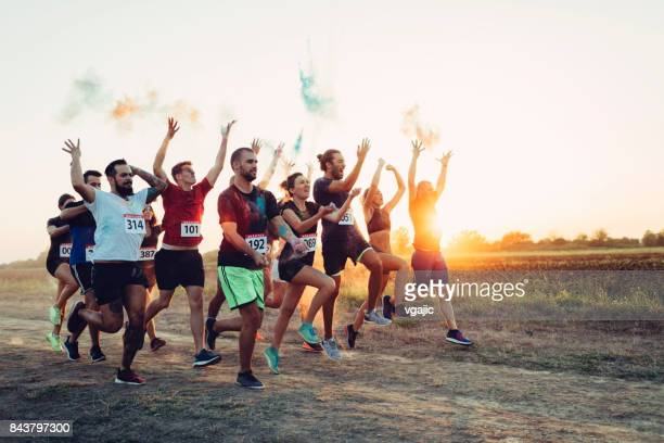 marathon racers throwing holi colors - sports team event stock photos and pictures