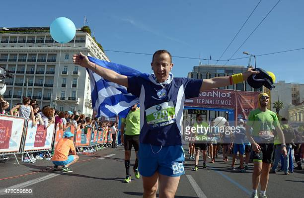 A marathon runner finishes the Half Marathon holding a Greek flag Over 3000 runners took part in the 4th Athens Half Marathon 2015 in Athens running...