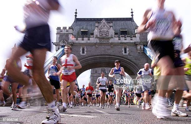 Marathon runners charge over London's Tower Bridge at the halfway mark in the London Marathon 22 April 2001 Over 30000 runners are expected to finish...