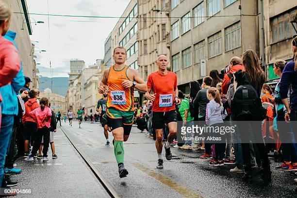 corredores de maratón compitiendo entre sí - carrera de calle fotografías e imágenes de stock