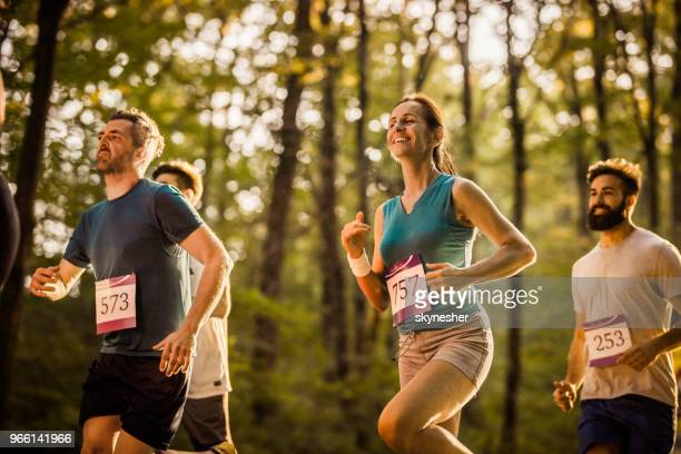 marathon runners having a race through the forest. - half_marathon stock pictures, royalty-free photos & images
