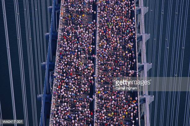 Marathon runners jogging across bridge, elevated view