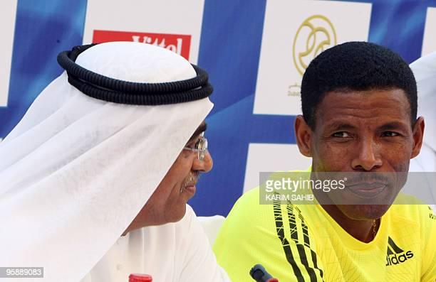 Marathon world record holder Haile Gebrselassie of Ethiopia sits next to Ahmed alKamali marathon general coordinator during a press conference in...