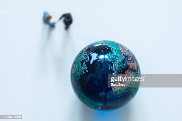 marble earth and two men shaking hands - world politics stock pictures, royalty-free photos & images