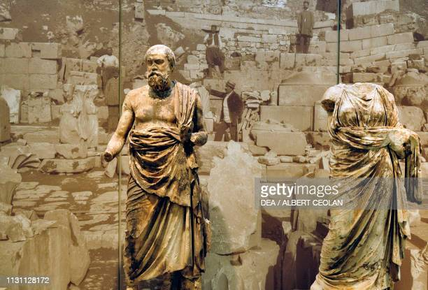 Marble statue of a Philosopher said to be either Plutarch or Plato with a photograph of the excavations at Delphi in the background Greece