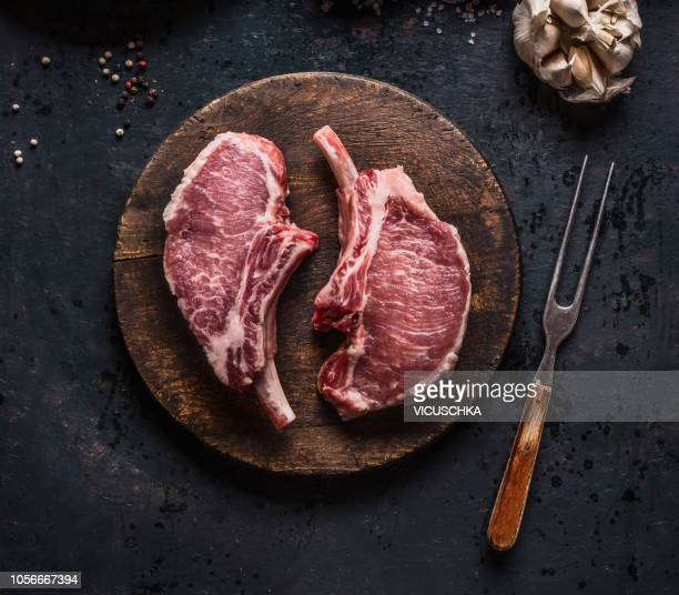 marbled raw pork chops of porco iberico meat on round cutting board with meat knife. french racks - roh stock-fotos und bilder