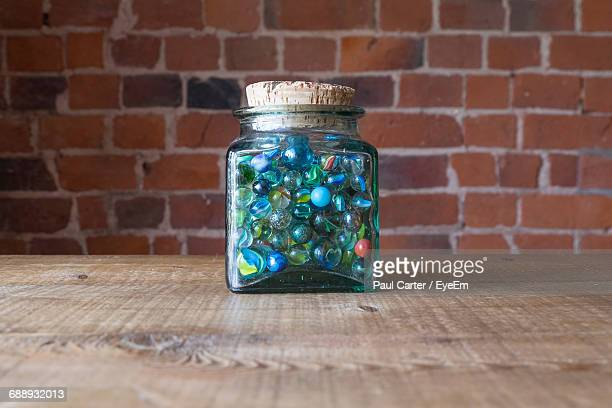 Marbles In Glass Jar On Table Against Brick Wall