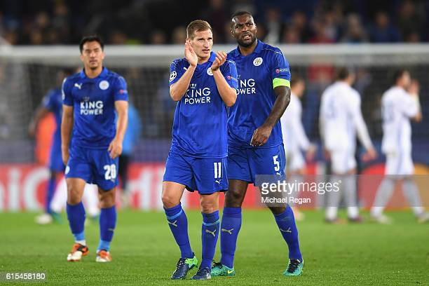 Marc Albrighton and Wes Morgan of Leicester City applaud supporters after the UEFA Champions League Group G match between Leicester City FC and FC...