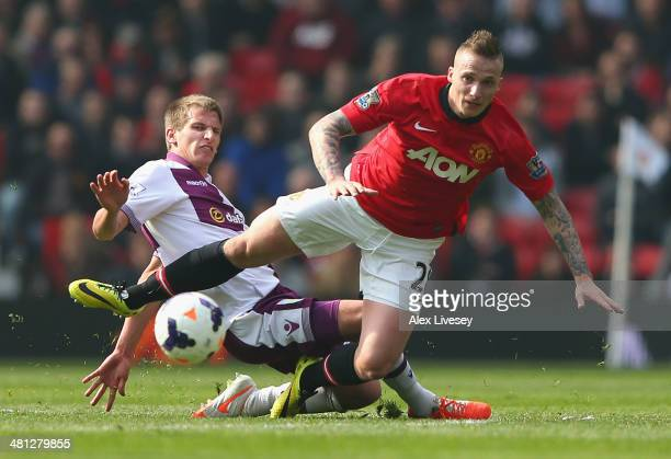 Marc Albrighton of Aston Villa challenges Alexander Buttner of Manchester United during the Barclays Premier League match between Manchester United...