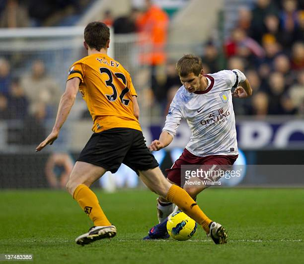 Marc Albrighton of Aston Villa is challenged by Kevin Foley of Wolverhampton Wanderers during the Barclays Premier League match between Wolverhampton...