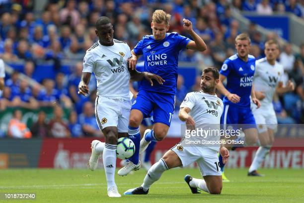 Marc Albrighton of Leicester battles with Willy Boly of Wolves and Jonny of Wolves during the Premier League match between Leicester City and...