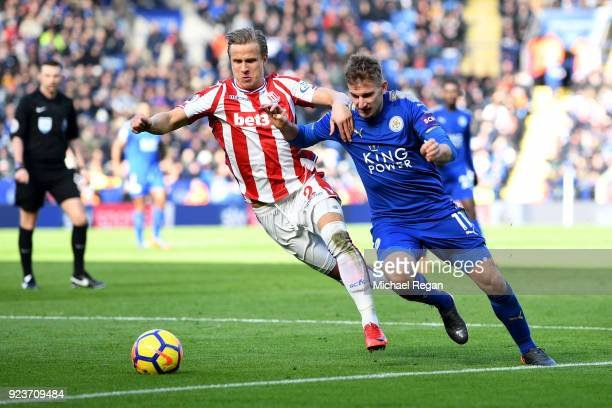 Marc Albrighton of Leicester City is challenged by Moritz Bauer of Stoke City during the Premier League match between Leicester City and Stoke City...