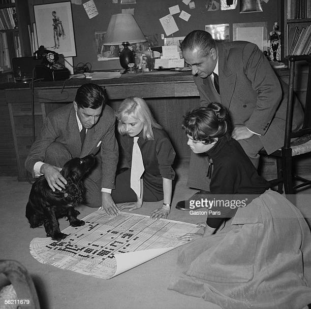 Marc Allegret Isabelle Pia and Brigitte Bardot examining the plan of shooting of film Futures vedettes at Marc Allegret France 1955