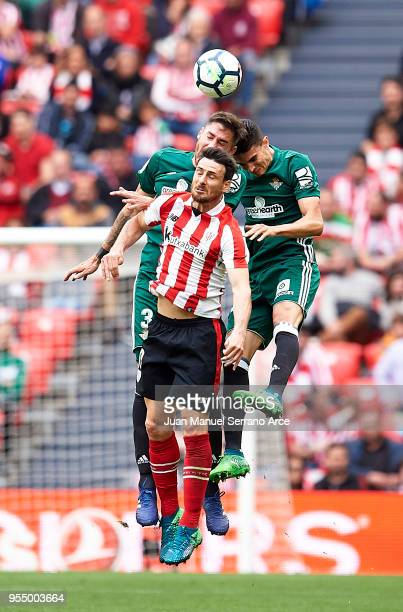 Marc Bartra and Javi Garcia of Real Betis competes for the ball with Aritz Aduriz of Athletic Club during the La Liga match between Athletic Club...