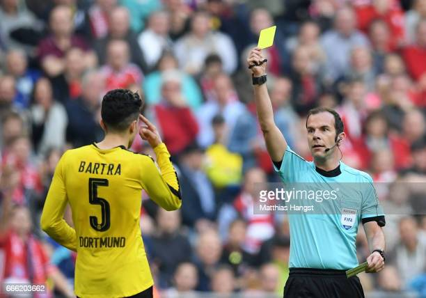 Marc Bartra of Borussia Dortmund is shown a yellow card by referee Marco Firtz during the Bundesliga match between Bayern Muenchen and Borussia...
