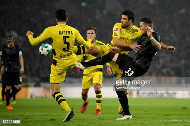 Marc Bartra of Dortmund and Sokratis Papastathopoulos of Dortmund challenge Daniel Ginczek of Stuttgart during the Bundesliga match between VfB...