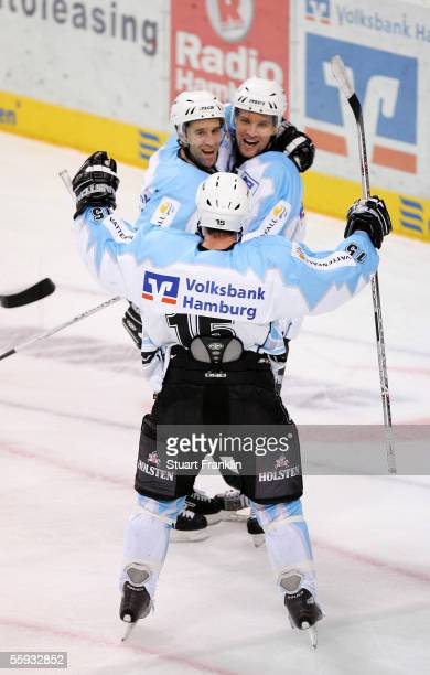 Marc Beaucage celebrates scoring the fourth goal with Benoit Gratton and Francois Fortier of Hamburg during the DEL match between Hamburg Freezers...